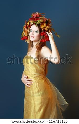Autumn Woman. Beautiful makeup. Golden dress. Dark blue and purple color background - stock photo