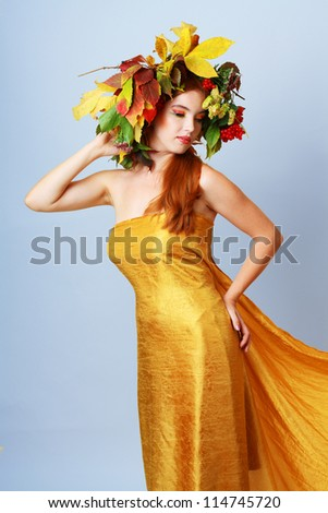 Autumn Woman. Beautiful makeup. Golden dress. Light blue gray background
