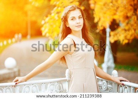 Autumn woman. Beautiful young trendy girl in autumn park - stock photo