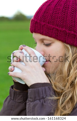 Autumn woman drinking a hot beverage  - stock photo