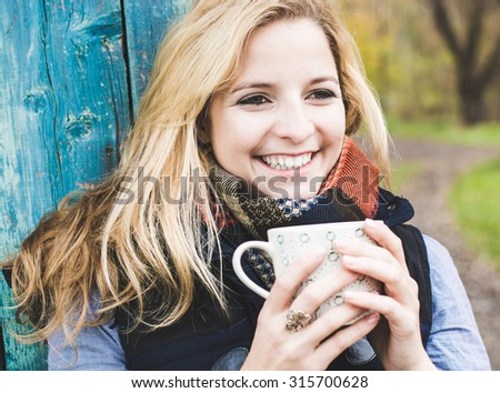 Autumn woman drinking coffee. Fall concept of young woman enjoying hot beverages over blue wooden wall. Caucasian female model in city forest park. - stock photo