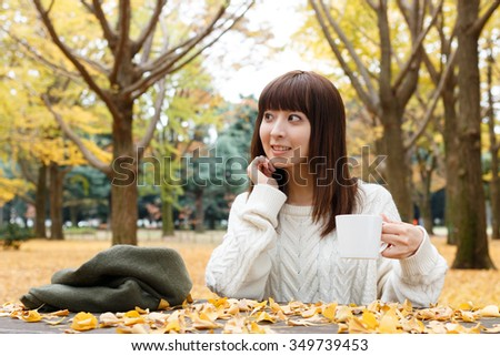 Autumn woman drinking coffee under fall foliage