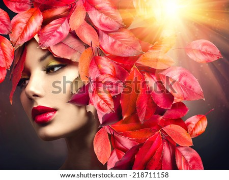 Autumn Woman Fashion Portrait. Fall. Beautiful Model Girl with colourful autumn leaves hairstyle. Red Autumn leaves Hair. Fashion Art design