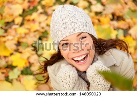 Autumn woman happy with colorful fall leaves in beautiful yellow forest foliage. Excited cheerful girl looking at camera joyful with beautiful autumn colors. Multiracial Asian Caucasian female model. - stock photo