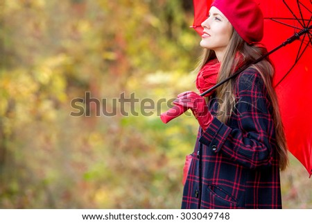 Autumn woman in autumn park with red umbrella, scarf and leather gloves - stock photo