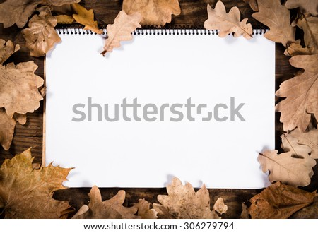Autumn wooden natural background with withered leaves and blank opened page of notebook - stock photo