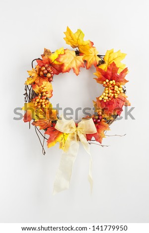 Autumn wreath hanging on a bright door - stock photo
