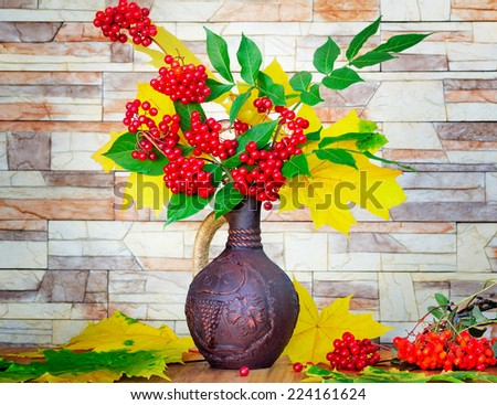 Autumn yellow leaves and bright red berries in a ceramic jug. Near are Rowan berries. Autumn still life. - stock photo