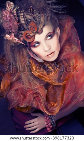 Autumn. Young woman with artistic visage and hairstyle and with dry leafs in her hair - stock photo