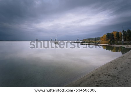 Autumnal cloudy landscape. A beautiful view at the lake with a lonely white yacht, moored near wooden pier.