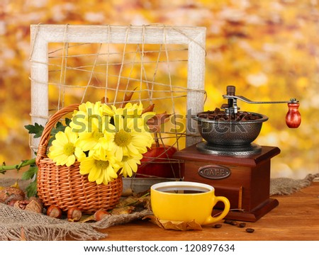 autumnal composition:coffee grinder, flowers  and leaves on bright background