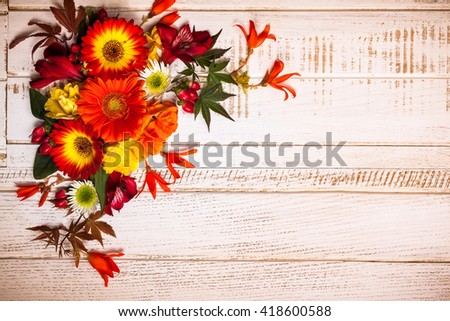 Autumnal flowers and berries on vintage wooden background. Top view with copy space - stock photo