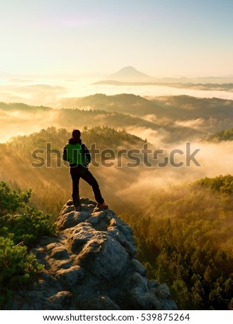 Autumnal  misty morning in nature. Hiker in black stand on peak in rock  and watching over the misty and foggy morning valley to Sun.