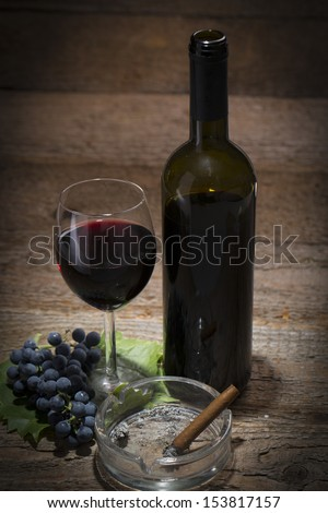 autumnal still life, grapes, wine glass, wine bottle and ashtray with cigar on old wooden