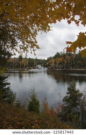 Autumnal tree branches overhang a calm body of water