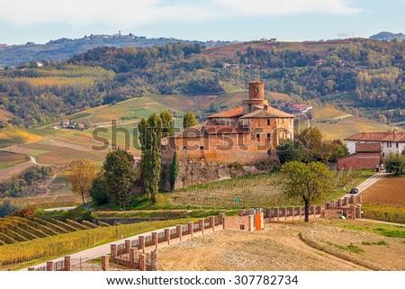Autumnal vineyards and Castello della Volta in Piedmont, Northern Italy. - stock photo