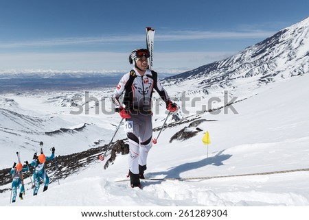AVACHA VOLCANO, KAMCHATKA, RUSSIA - APRIL 26, 2014: Aleksei Zagorski rises (with skis strapped to backpack) on volcano. Individual race ski mountaineering Asian, ISMF, Russian, Kamchatka Championship. - stock photo