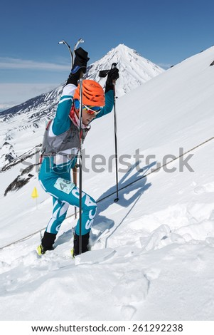 AVACHA VOLCANO, KAMCHATKA, RUSSIA - APRIL 26, 2014: Catherine Osichkina rises (skis strapped to backpack) to volcano. Individual race ski mountaineering Asian, ISMF, Russian, Kamchatka Championship. - stock photo