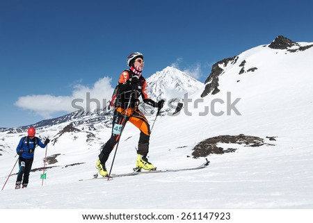AVACHA VOLCANO, KAMCHATKA, RUSSIA - APRIL 26, 2014: Chinese ski mountaineer Ma Nan climbs on skis on volcano. Individual race ski mountaineering Asian, ISMF, Russian and Kamchatka Championship.