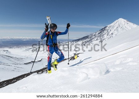 AVACHA VOLCANO, KAMCHATKA, RUSSIA - APRIL 26, 2014: Ski mountaineer Baranov Denis climbs to mountain with skis strapped to backpack. Individual race ski mountaineering Asian, ISMF, Russian Championship - stock photo