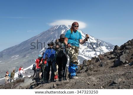 AVACHA VOLCANO, KAMCHATKA, RUSSIA - JULY 08, 2014: Hiking on Kamchatka Peninsula - a group of tourists go hiking and climbing to top of Avacha Volcano on background of Koryak Volcano. Russia, Far East - stock photo