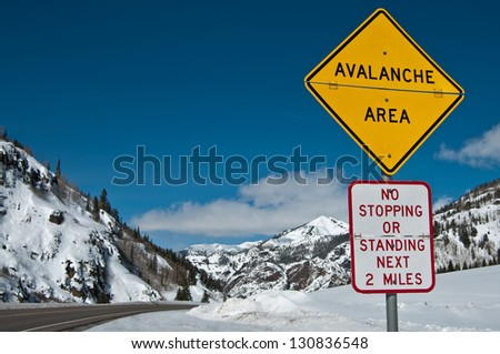 Avalanche Area Sign:  A convertible sign alerts winter travelers to possible snow slides in the Rocky Mountains of southwest Colorado. - stock photo