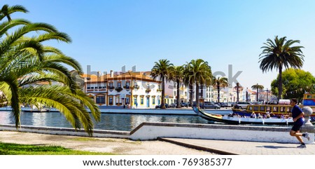 "Aveiro / Portugal August 13, 2017: Man doing sport next to the village canal and typical boats of Aveiro called ""moliceiros"", with paklmeras, typical houses and a blue sky"