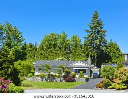 Average family house in beautiful calm place. Residential house with landscape on elevated ground terrace in front and blue sky background. Family house with asphalt driveway and  detached garage. - stock photo