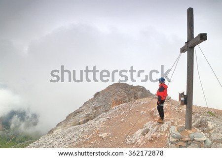 Averau peak and woman climber standing near large wooden cross above the clouds, Dolomite Alps, Italy