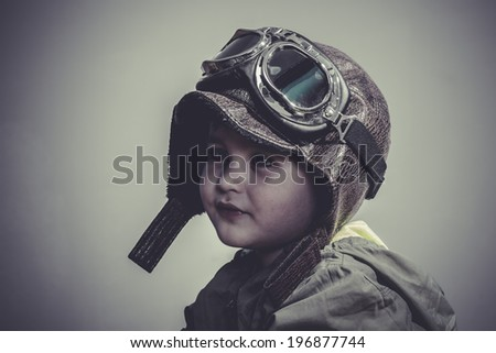 aviation, fun and funny child dressed in aviator hat and goggles - stock photo