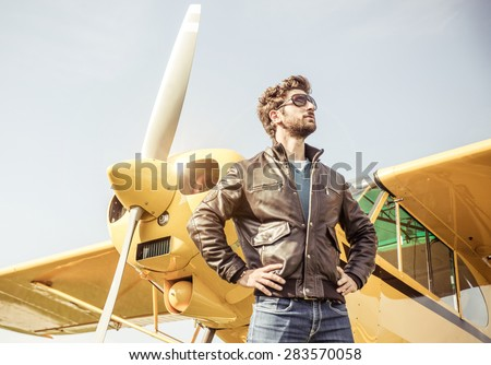 aviator posing before flight with his aircraft. concept about airplanes,pilots and people - stock photo