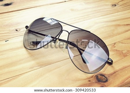 Aviator sunglasses on a wooden board, Classic sunglasses. (Vintage Style Color)