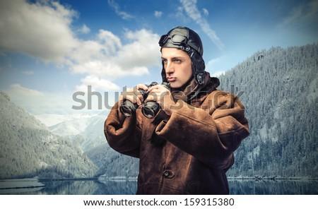 aviator with binoculars in the mountain - stock photo