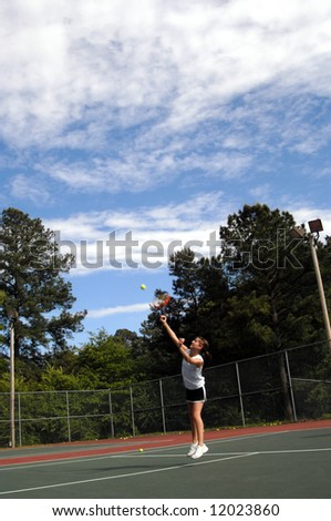 Avid tennis fan returns tennis volley.  Uniform is black skirt and white tee shirt. - stock photo