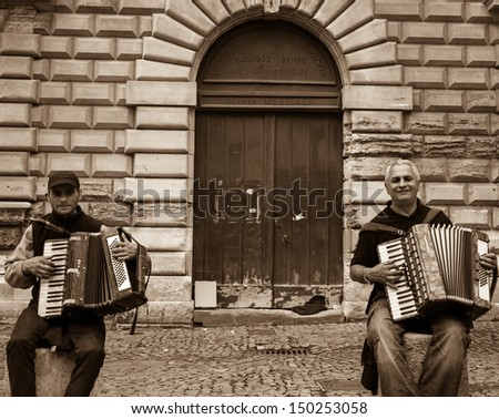 AVIGNON, FRANCE - APRIL 30: Two unidentified street musician near doors of National Music School as seen on April 30, 2013 in Avignon, France. Hundreds of buskers perform on the streets in France. - stock photo