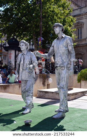 AVIGNON, FRANCE - JUL 12, 2014:  An unidentified busking mimes. Living statues entertain the tourists during the annual Avignon Theater Festival in Avignon. - stock photo