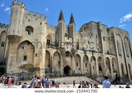AVIGNON, FRANCE - JUL 12, 2014: Tourists near  Popes Palace Avignon.  Popes Palace is the main historical site in Provence and one of the largest and most important medieval Gothic buildings in Europe - stock photo