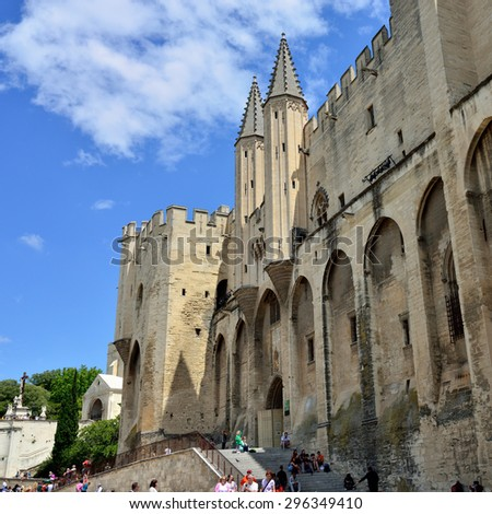 AVIGNON, FRANCE - JULY 12, 2014: Tourists on the square of Popes Palace Avignon. Palace is the main historical site in Provence and one of the largest and important medieval Gothic buildings in Europe