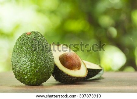 Avocado and avocado pieces on a wooden floor and has a background of nature; Selected focus - stock photo