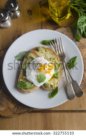 Avocado and poached egg on Rye with basil - stock photo