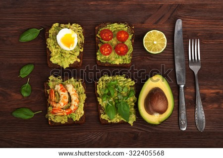 Avocado; avocado oil; sandwich; bread and butter; wad; dodger; avocado puree; sandwich with shrimp; sandwich with egg; tomatoes; cherry; basil; Rye bread; useful bread; bread with mashed avocado; - stock photo