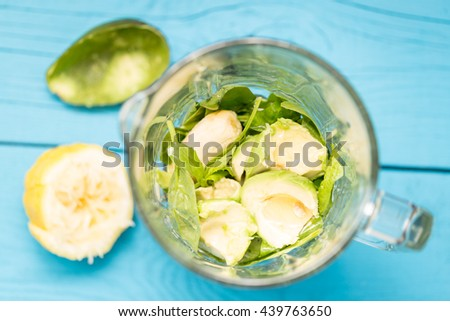 Avocado, Banana, Lemon Juice, Spinach and Almond Milk in Mixer, Absolutely Amazing Tasty Green Avocado Shake or Smoothie Preparation Process, Blue Wooden Background, Raw, Vegan Drink, Top View - stock photo