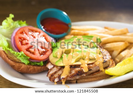 Avocado chicken burger with fries - stock photo
