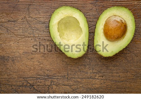 avocado cut in half on a grunge wood with a copy space - stock photo