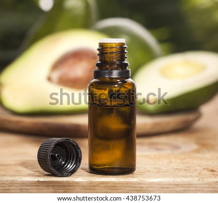 Avocado Essential Oil on tropical green leaves background and wooden table. Horizontal. Front view.
