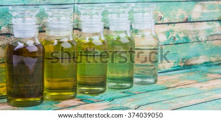 Avocado fruit oil, sesame seed oil, olive oil, grape seed oil and corn oil in vial glass bottle over rustic wooden background