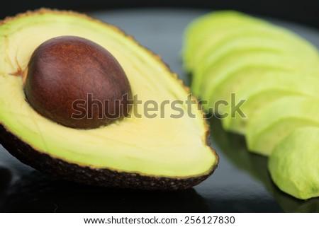 Avocado fruit on black floor - stock photo