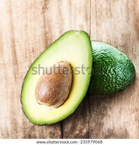 Avocado fruit over wooden background. Fresh green Avocado fruit macro  - stock photo