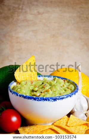 Avocado guacamole dip with ingredients on a wooden background - stock photo