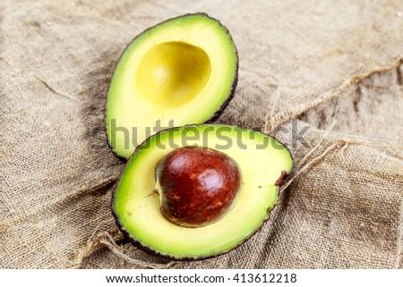 avocado halves on burlap background - stock photo